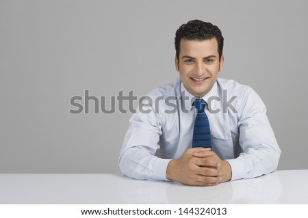Businessman smiling with hands clasped - stock photo
