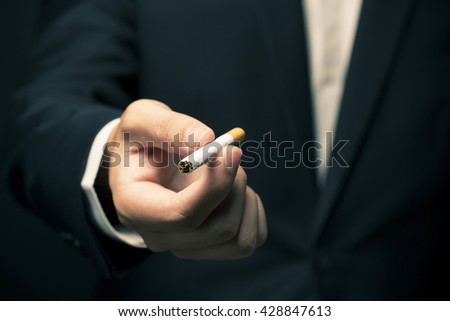 Businessman smoking a cigarette - stock photo