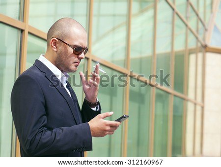 Businessman smoking and looking on cellphone - stock photo
