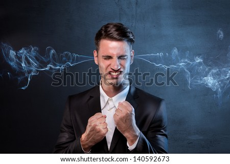 Businessman smoking from ears with anger - stock photo