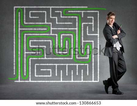 Businessman solved a maze on a wall - stock photo