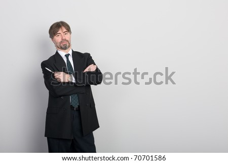 Businessman standing against a blank gray wall. - stock photo