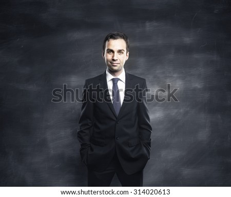businessman standing against a gray wall - stock photo