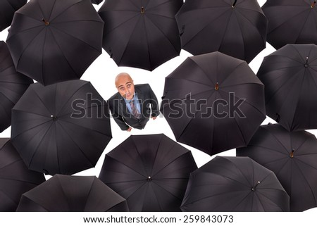 Businessman standing amongst black umbrellas isolated in white - stock photo