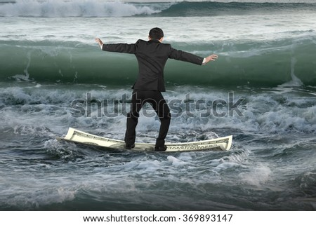 Businessman standing and balancing on money boat floating in the ocean with oncoming waves - stock photo