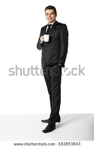 Businessman standing and drinking coffee against white background. - stock photo