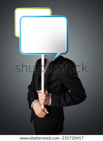Businessman standing and holding an empty speech bubble in front of his head - stock photo
