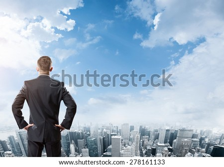 Businessman standing and looking at the city - stock photo