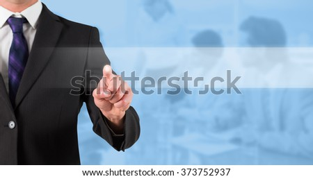 Businessman standing and pointing against blue background - stock photo