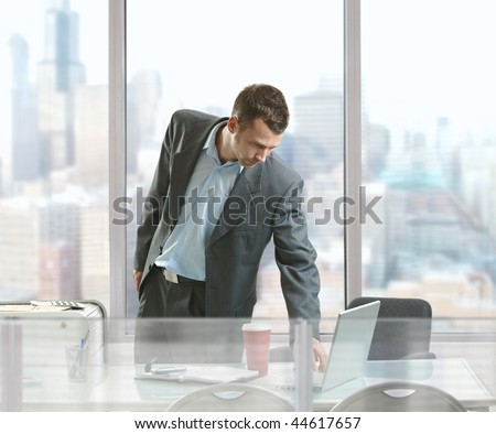 Businessman standing at desk in front of office windows, using laptop computer. - stock photo