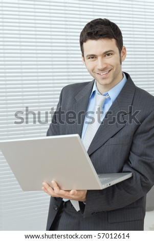 Businessman standing at office holding laptop computer in hand, working. - stock photo