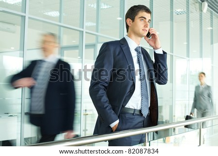 Businessman standing by banisters and calling with walking people on background - stock photo