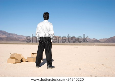 Businessman standing by shipping boxes - stock photo