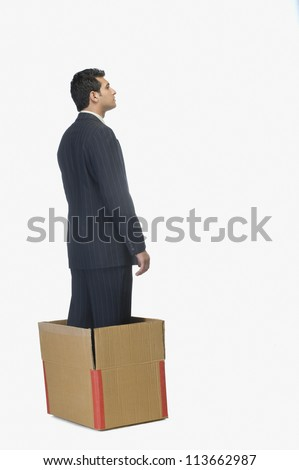 Businessman standing in a cardboard box - stock photo
