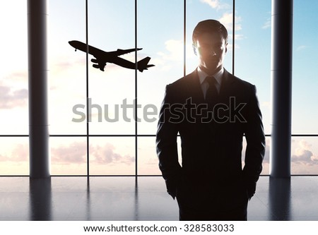 businessman standing in airport and airplane in sky - stock photo