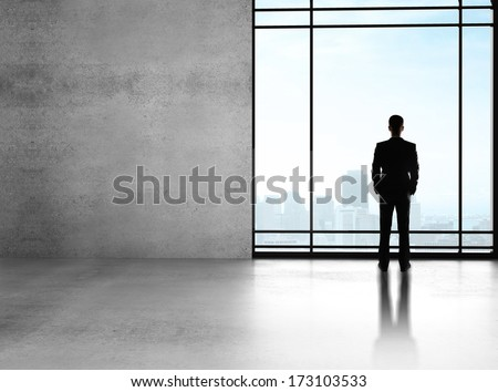 businessman standing in big sunlight office with window - stock photo