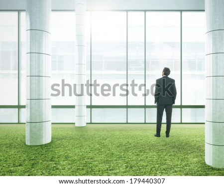 Businessman standing in bright office with green grass floor - stock photo