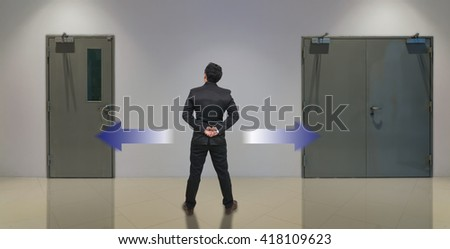 Businessman standing in doubt,thinking the two different choices indicated by arrows pointing in opposite direction, business decision concept - stock photo