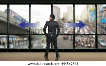 Businessman standing in doubt,thinking the two different choices of transportation for traffic jam with rush hour which indicated by arrows pointing in opposite direction, business decision concept - stock photo