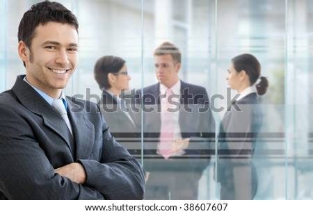 Businessman standing in downtown office, businesspeople talking in background in front of windows. - stock photo