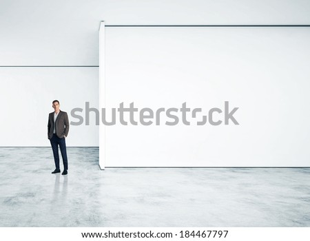 Businessman standing in empty bright office - stock photo