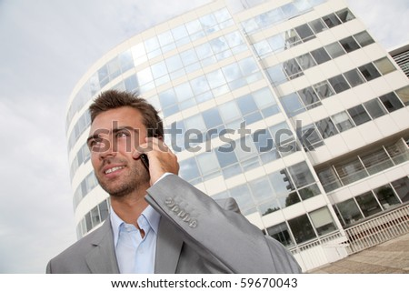 Businessman standing in front of building with telephone - stock photo