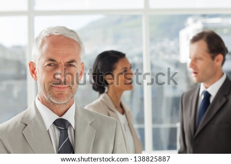 Businessman standing in front of colleagues speaking together in their office - stock photo