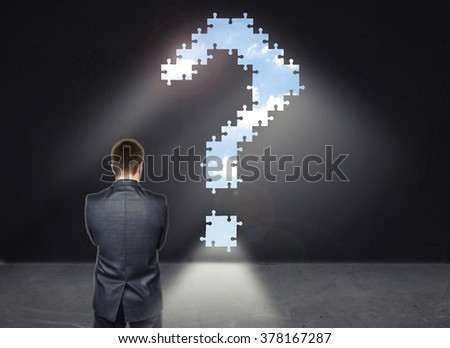 Businessman standing in front of the wall with big question mark looking like way out room - stock photo