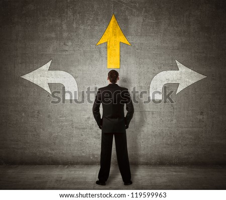 Businessman standing in front of three arrows - stock photo