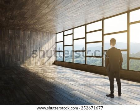 Businessman standing in modern empty interior - stock photo