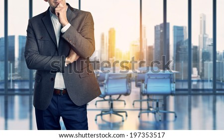 Businessman standing in modern office - stock photo