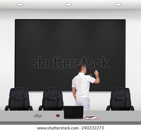 businessman standing in office and drawing on blackboard - stock photo