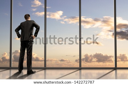 businessman standing in office and looking in sky - stock photo