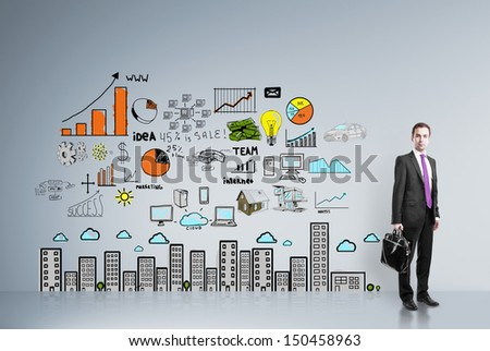 businessman standing in room with drawing  business strategy on wall - stock photo