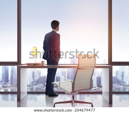 Businessman standing in sunny office and looking city - stock photo