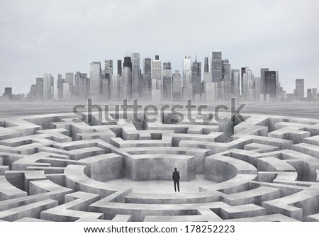 Businessman standing in the middle of a maze. Big city on a horizon. - stock photo