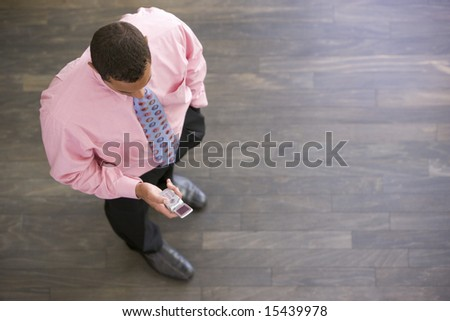 Businessman standing indoors looking at cellular phone - stock photo