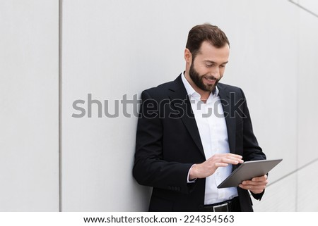 Businessman standing leaning against a wall using a tablet computer smiling as he reads the screen - stock photo