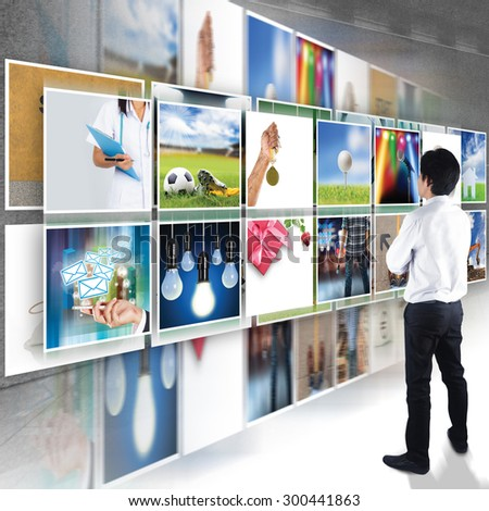 Businessman standing looking at Digital photo gallery images streaming, TV screen  - stock photo