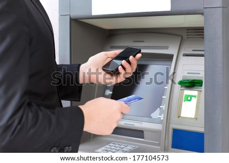businessman standing near the ATM and holding a credit card and mobile phone in hands - stock photo