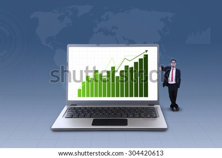 Businessman standing next to laptop with increasing bar chart on blue world map background - stock photo