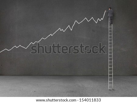 Businessman standing on a giant ladder and writing a chart - stock photo