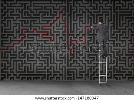Businessman standing on a ladder and drawing a red line through black maze on a wall - stock photo
