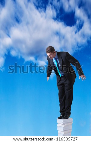 businessman standing on a large pile of paper going right up into the sky - stock photo