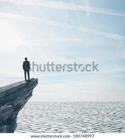 Businessman standing on a rock and looking at huge maze - stock photo