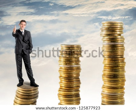 Businessman standing on a stack of money - stock photo