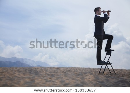 Businessman standing on chair and looking through telescope in desert - stock photo