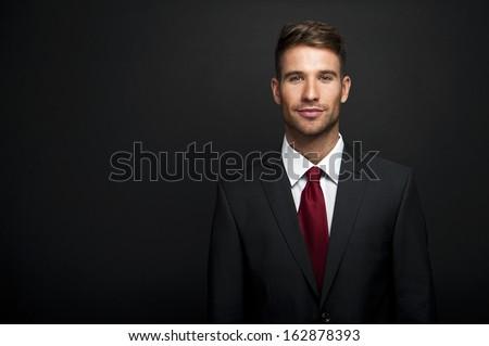 Businessman standing on dark gradient background - stock photo