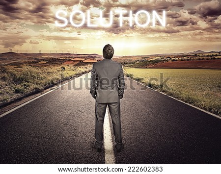 Businessman standing on highway over beautiful sky background. Concept of straight path to problem solution. - stock photo