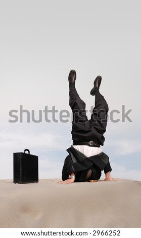 Businessman standing on his head with his head in the sand - stock photo